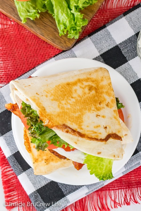 Overhead picture of a white plate with a pan fried BLT tortilla wrap on it