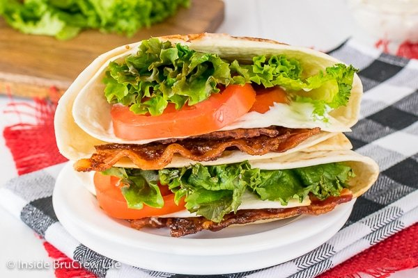 Close up picture of a white plate with a BLT tortilla wrap stuffed with bacon, lettuce, and tomatoes on it