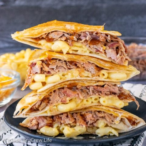 A black plate with pulled pork macaroni and cheese tortilla wraps cut in half and stacked on top of each other