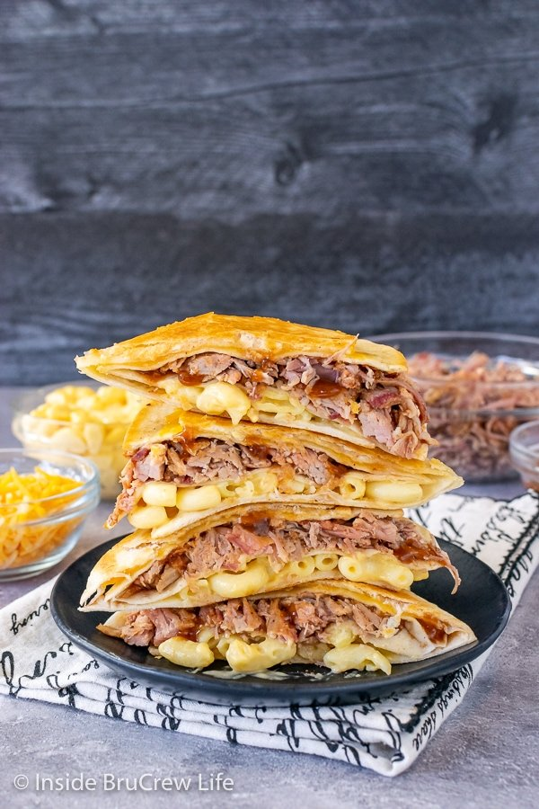 A black plate on a towel with pulled pork macaroni and cheese wraps cut in half and stacked on top of each other showing the filling
