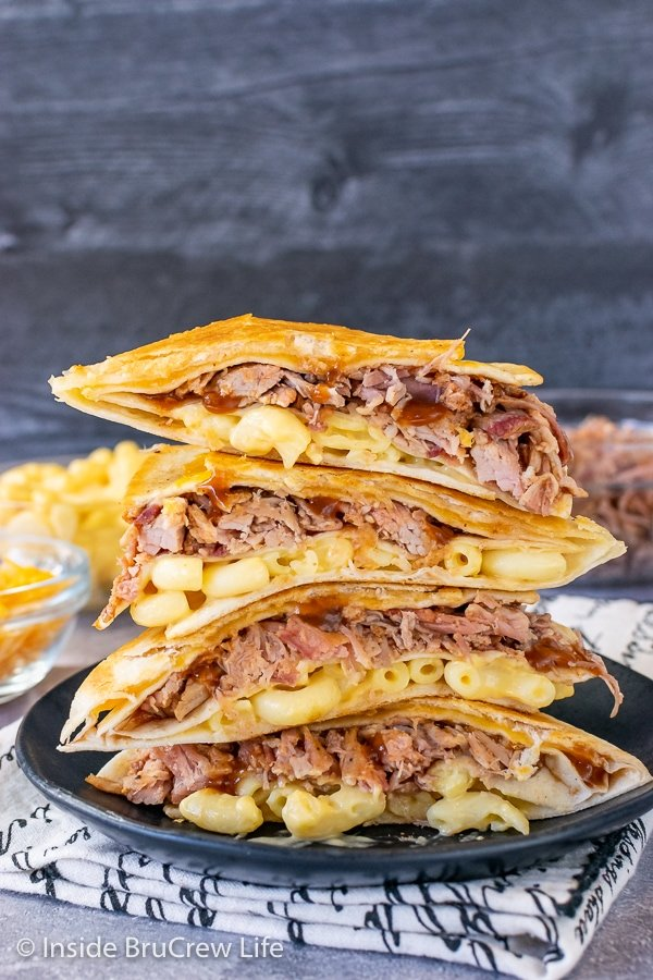 Four pulled pork macaroni and cheese tortilla wraps stacked on top of each other on a black plate showing the inside fillings