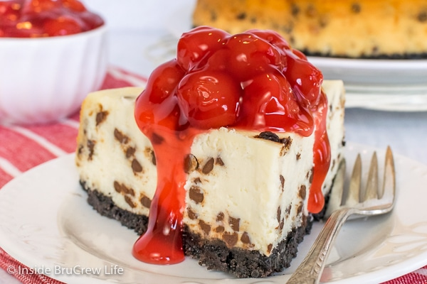 A slice of chocolate chip cheesecake on a white plate topped with cherry pie filling