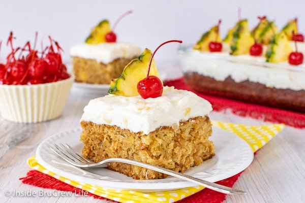 A white plate with a square of homemade pineapple cake topped with pineapple frosting and cherries