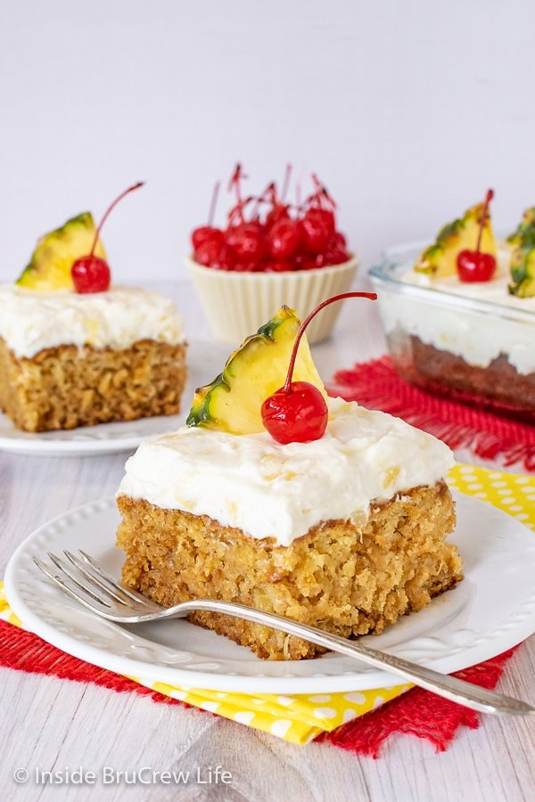 Two white plates with pineapple cake topped with pineapple cream cheese frosting, cherries, and pineapple slices.