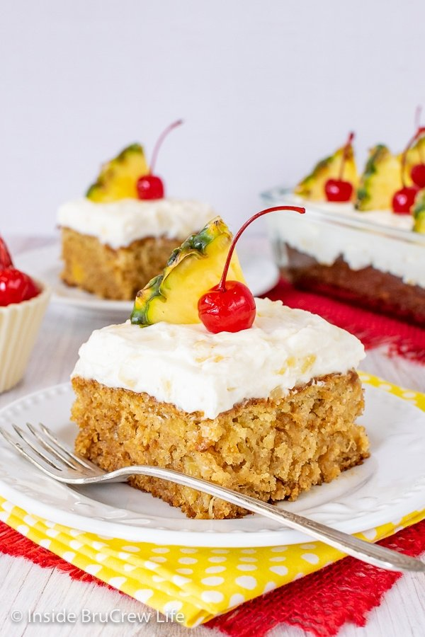 Two white plates with squares of pineapple sunshine cake topped with pineapple frosting and cherries on them