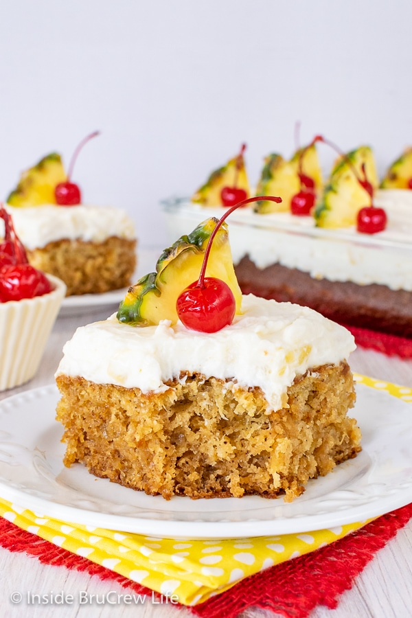 A white plate with a piece of pineapple sunshine cake topped with pineapple cream cheese frosting, a cherry, and pineapple slice on it