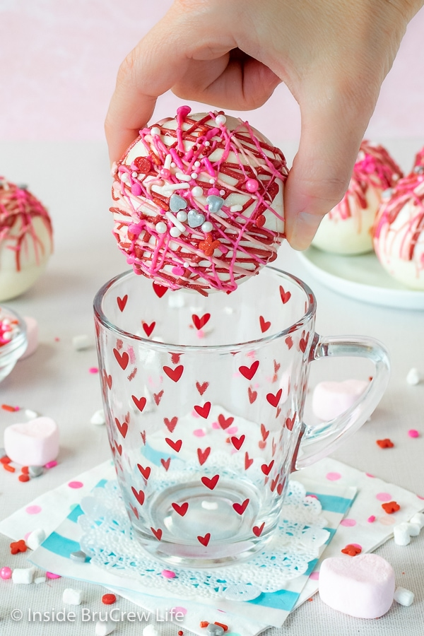 An empty clear mug with red hearts on a doily with a strawberry white hot chocolate bomb being held above it