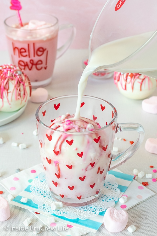 A clear mug with red hearts with a strawberry hot chocolate bomb in it and milk being poured over it