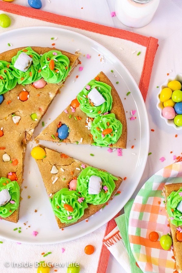 An overhead picture of a white plate with slices of Easter cookie cake with green frosting and sprinkles on it