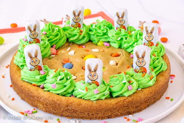 A full Easter cookie cake decorated with green frosting, candy, and Easter bunnies.