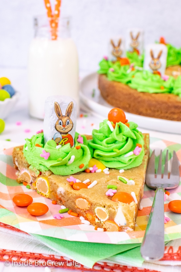 A slice of easy cookie cake with green frosting and chocolate bunnies on a pastel plate with more cookie cake behind it