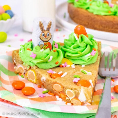 A slice of chocolate chip cookie cake decorated with green frosting and candies for Easter