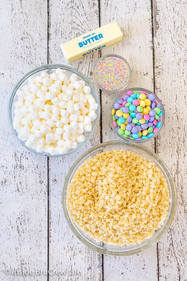 A white board with the ingredients to make Easter rice krispies treats in bowls