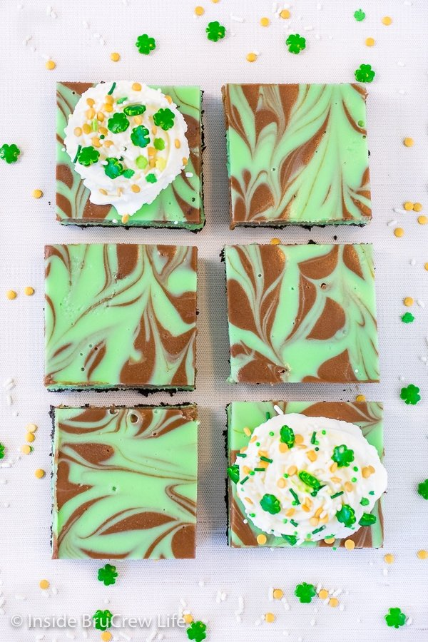 Overhead picture of a white board with squares of grasshopper cheesecake bars with chocolate swirls in them on it