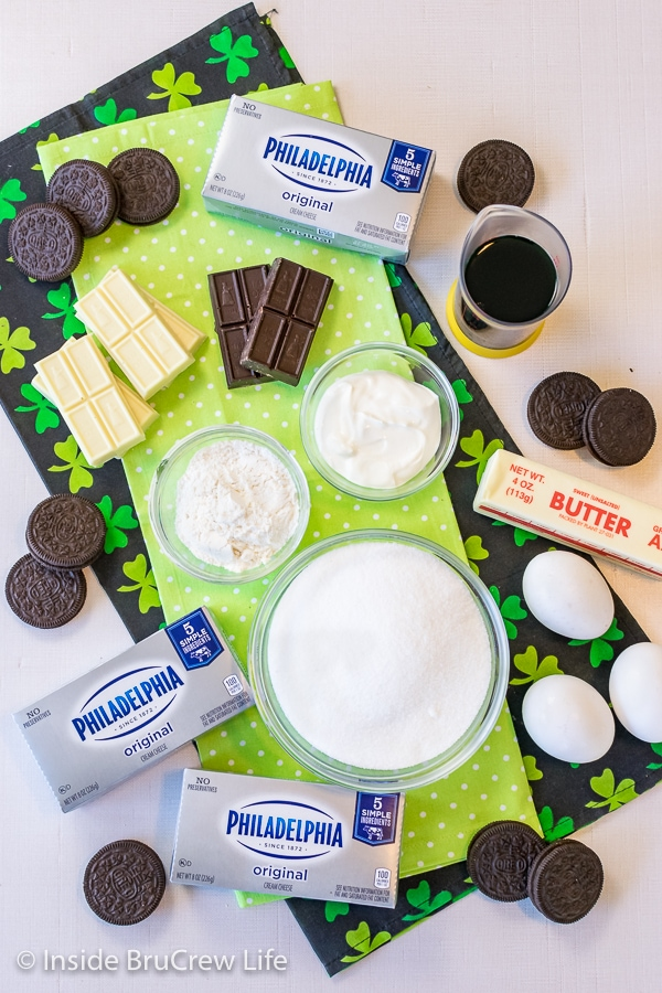 Overhead picture of a white board with the ingredients to make grasshopper cheesecake bars.