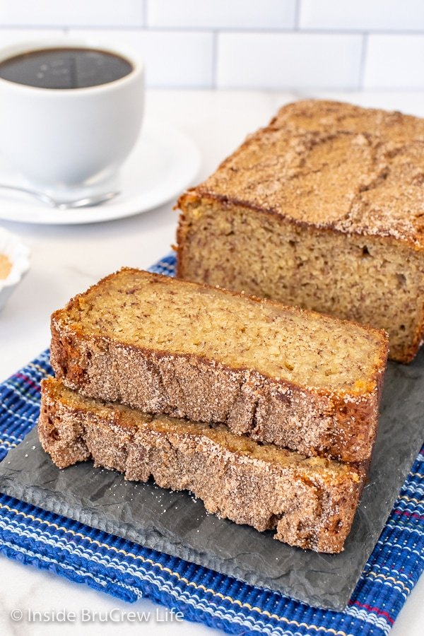 A gray tray with a loaf of cinnamon banana bread on it with two slices lying down in front