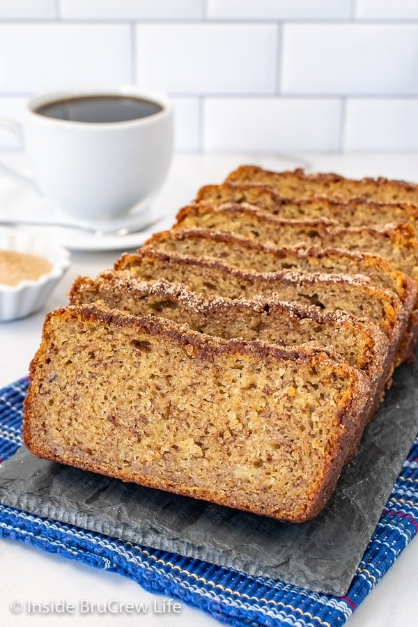 Slices of cinnamon banana bread standing up on a gray slate tray