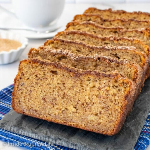 Slices of cinnamon banana bread stacked up on a slate tray