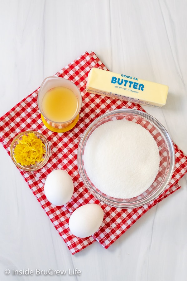A red and white checkered towel with bowls of ingredients needed for making an easy homemade lemon curd