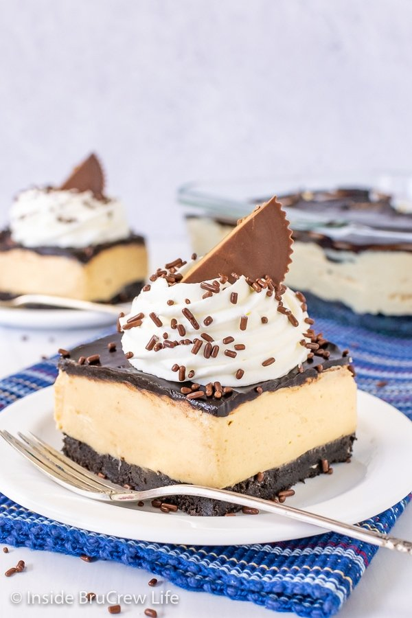 Two white plates on a blue towel with peanut butter pie bars topped with whipped cream, sprinkles, and peanut butter cups on them