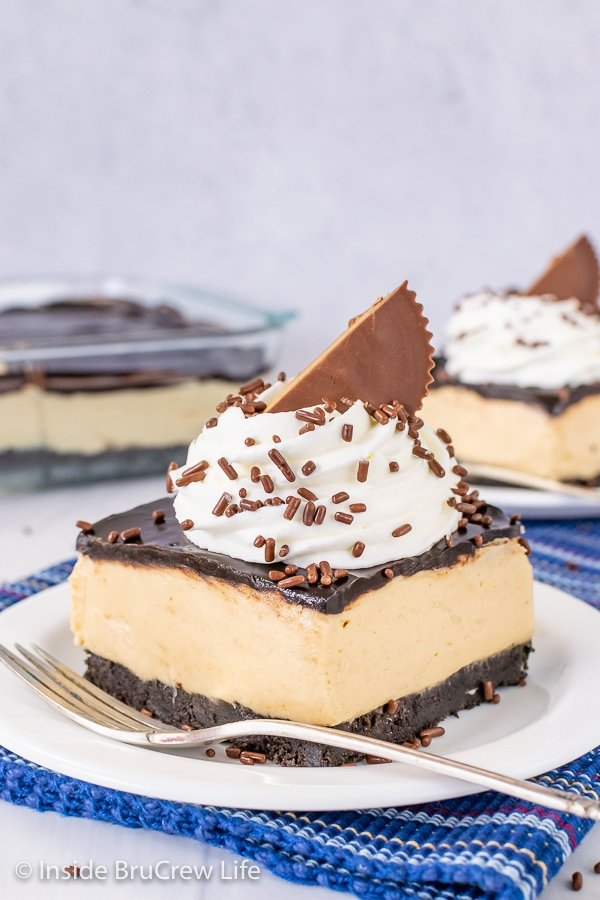 A white plate with a square of peanut butter pie bars topped with whipped cream and a peanut butter cup on it