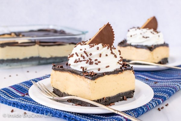 Two white plates with peanut butter squares topped with chocolate, whipped cream, and peanut butter cups on them
