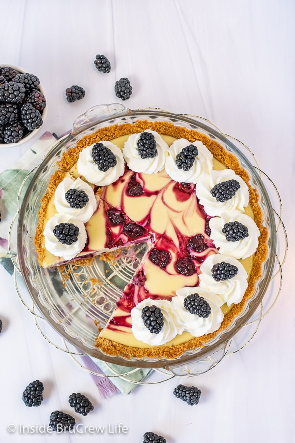 Overhead picture of the of a swirled blackberry cheesecake pie with whipped cream and fresh berries