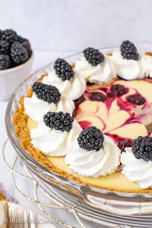 A close up of the side of a cheesecake pie with whipped cream swirls and fresh blackberries
