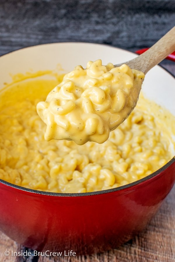 A red pot filled with creamy mac and cheese and spoon lifting some out