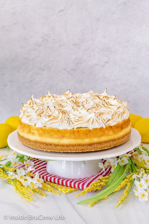 A white cake plate surrounded by white and yellow flowers with a lemon cheesecake topped with toasted meringue topping on it.