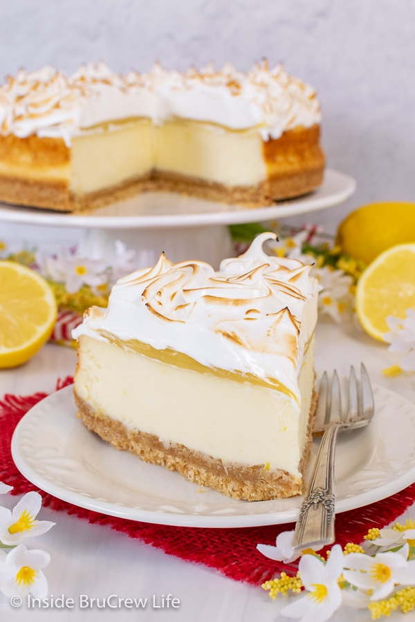 A white plate on a red towel with a slice of lemon cheesecake topped with lemon curd and toasted meringue topping on it and more cheesecake behind it