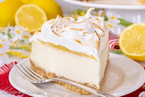 A white plate on a red towel with a slice of lemon meringue cheesecake and a fork on it and lemons behind it