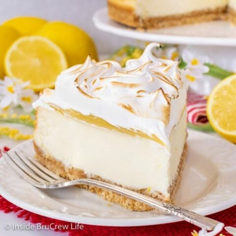A white plate with a slice of lemon cheesecake topped with lemon curd and marshmallow meringue on it