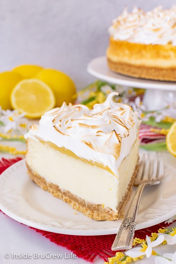 A slice of lemon cheesecake topped with lemon curd and meringue topping on a white plate with a fork