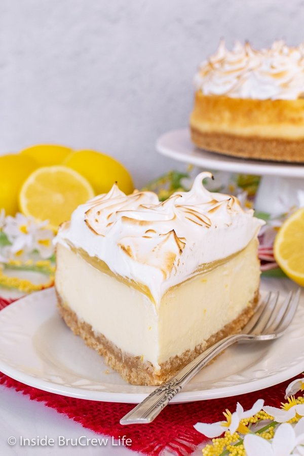 A white plate with a large slice of lemon cheesecake topped with lemon curd and a toasted meringue topping on it