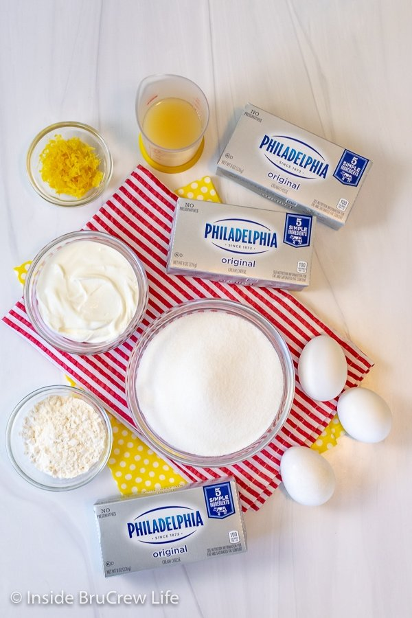 A white board with bowls filled with ingredients needed to make lemon meringue cheesecake on it