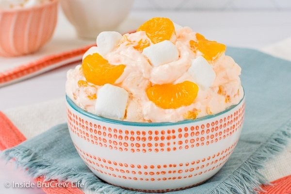 A blue towel with a white and orange bowl on it that is filled with orange fluff salad.