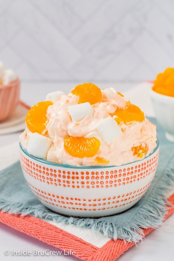 A white and orange bowl on a blue towel filled with Orange Fluff and topped with extra oranges.