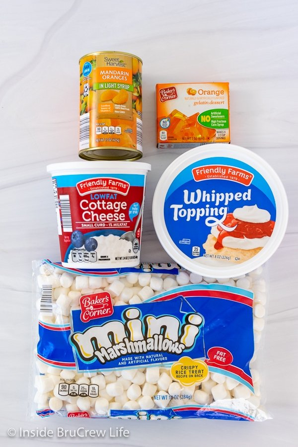 Overhead picture of the ingredients needed to make orange fluff dessert on a white board.