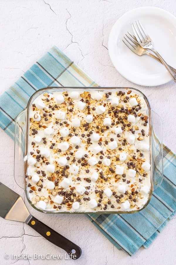 Overhead picture of a pan of chocolate icebox cake topped with whipped cream, marshmallows, nuts, and chocolate chips.