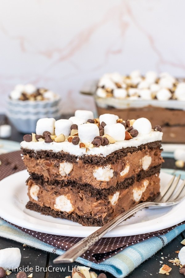 A white plate with a square of chocolate icebox cake topped with marshmallows and nuts on it.
