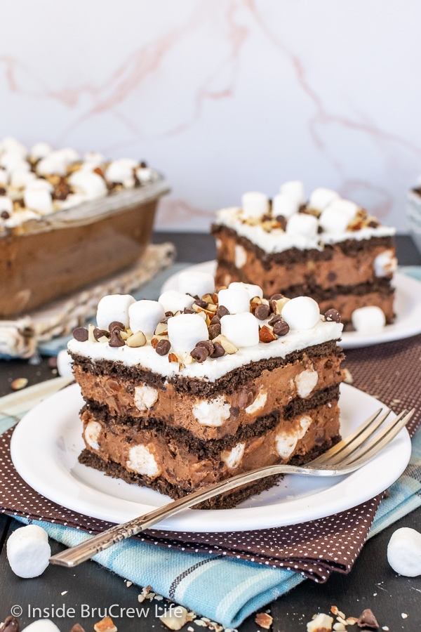 Two white plates with squares of chocolate icebox cake topped with marshmallows, nuts, and chocolate chips with a pan of dessert behind.