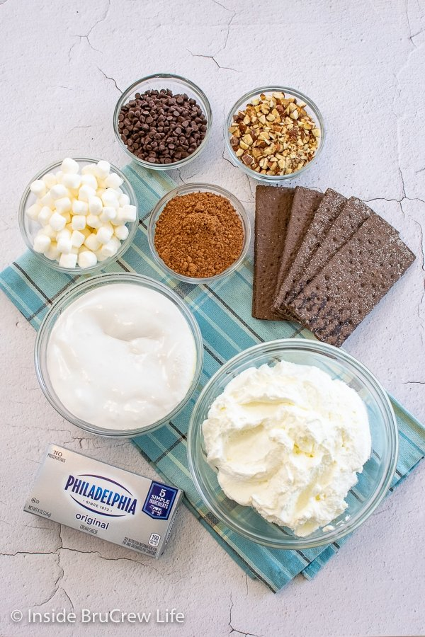 Bowls of ingredients to make a rocky road icebox cake on a white board.