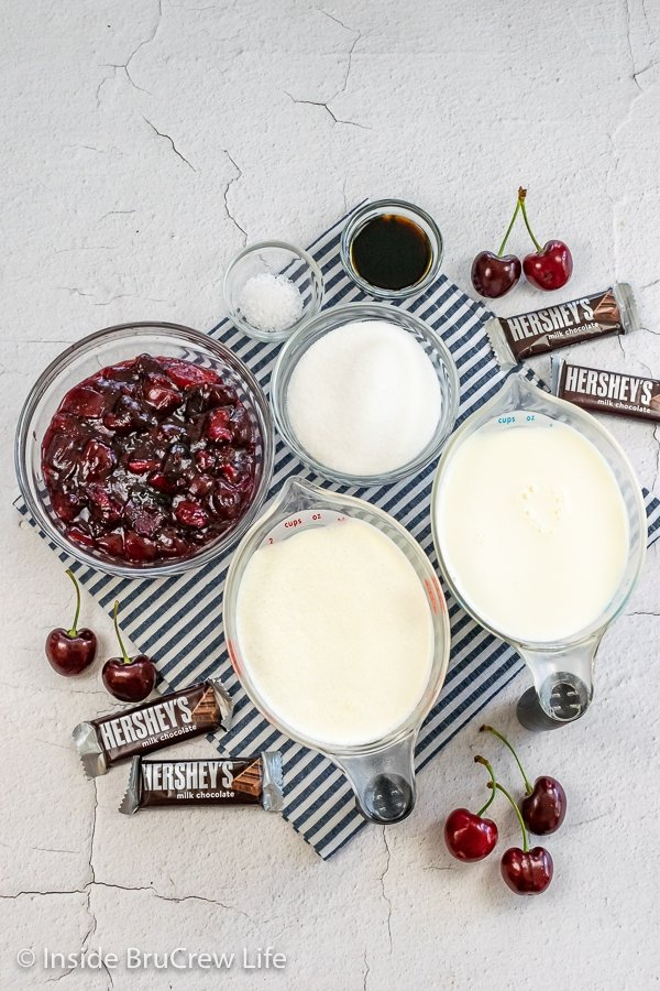 A white board with bowls of ingredients to make a homemade vanilla ice cream with cherry pie filling.
