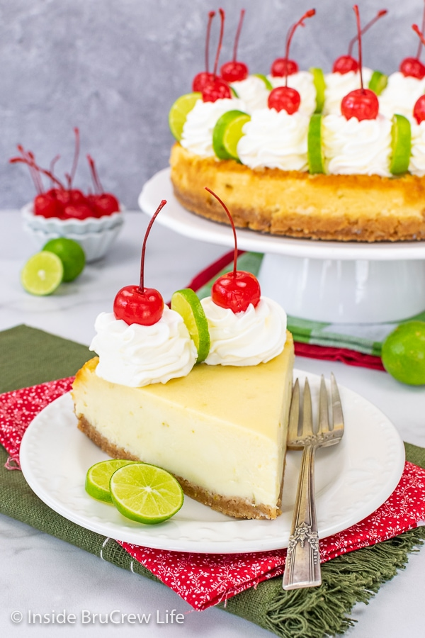 A white plate with a slice of key lime cheesecake on it and a plate with the rest of the cheesecake behind it.