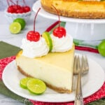 A white plate with a slice of key lime cheesecake with whipped cream and cherries on it.