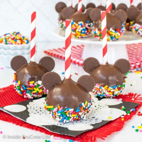 Three mickey mouse cake pops dipped in chocolate and colorful sprinkles with red and white straws.