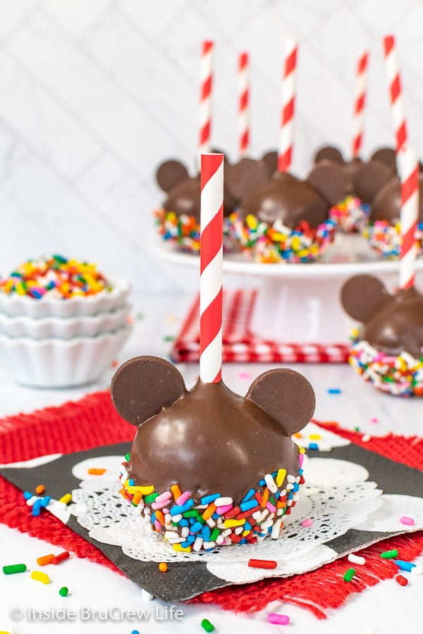One Mickey Mouse Cake Pop with colorful sprinkles on a white doily and a cake plate with more chocolate cake pops behind it.