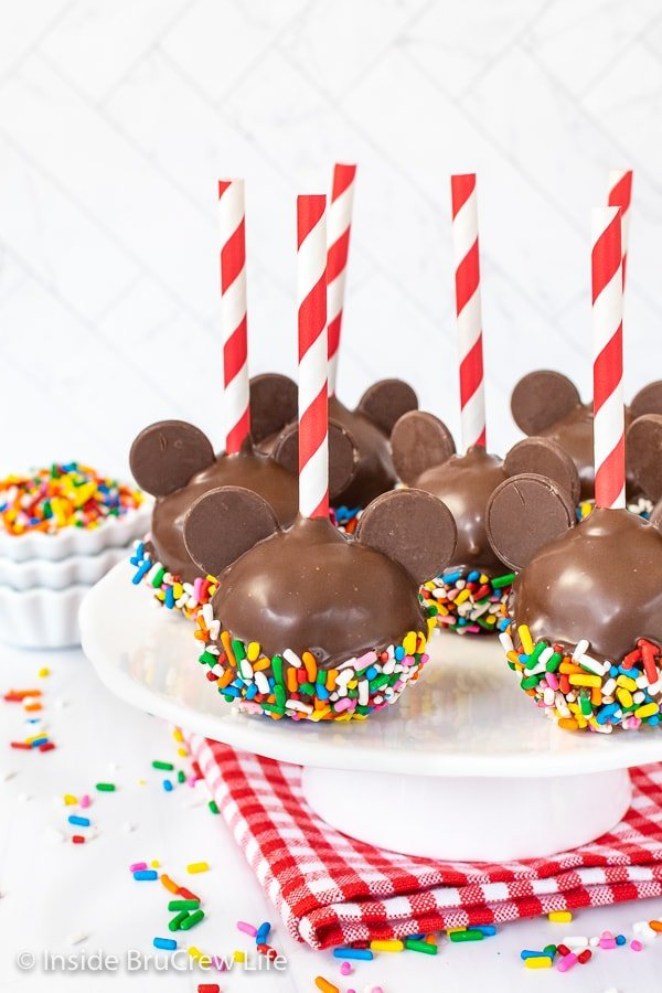 A white cake plate with seven Mickey cake pops with red and white straws on it.