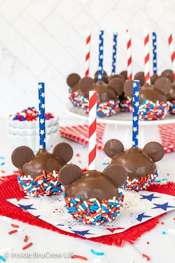 Three Mickey cake pops with red white and blue sprinkles and straws on them.